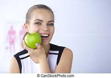 Young beautiful smiling girl with a green apple in hands