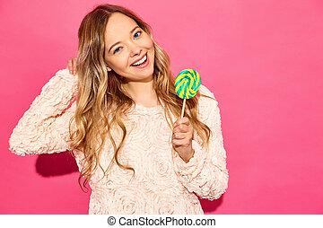 Young beautiful smiling hipster girl in trendy summer clothes. Sexy carefree woman posing near pink wall. Positive model eating lollipop