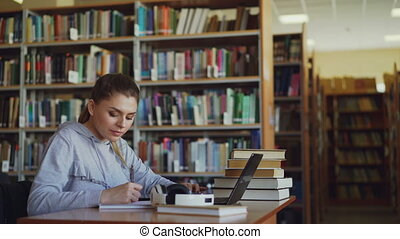 Young beautiful smiling student girl is sitting at desk in...