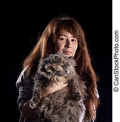 Young beautiful smiling woman holds fluffy cat