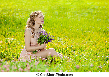 Young beautiful smiling woman in the field, on the grass. Girl r