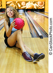 Young beautiful smiling woman sits on floor and holds pink ball in bowling club