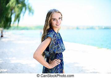 Young beautiful smiling woman wearing elegant dress posing standing on beach near the sea coast