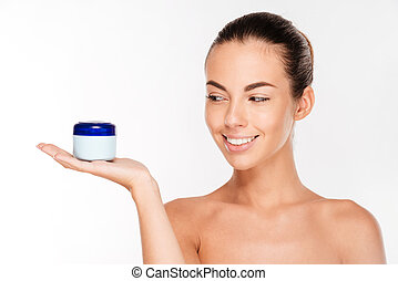 Young beautiful smiling woman with cream bottle