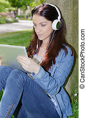 young beautiful smiling woman with tablet outdoors