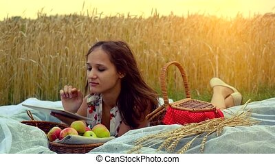 Young beautiful smiling woman with tablet pc on picnic in wheat field. 4k