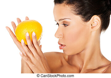 Young beautiful spa woman with orange in her hand