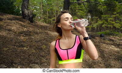 young beautiful sport girl drinks water