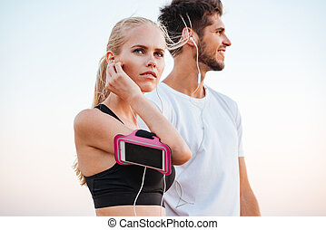 Young beautiful sports couple getting ready for a marathon