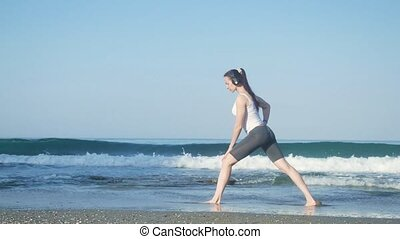 young beautiful sportswoman doing exercises on beach.