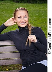 Young beautiful sporty brunette woman sitting on a bench in a park