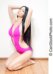 Young beautiful sporty girl with luxurious long hair sitting...