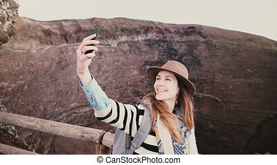 Young beautiful student girl with backpack smiling taking smartphone selfie photo on edge of Vesuvius volcano crater. Successful female travel blogger sharing emotion with friends on social networks.