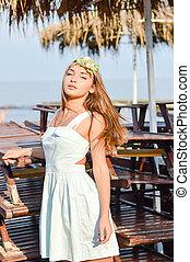 Young beautiful stylish blond woman on sea pier