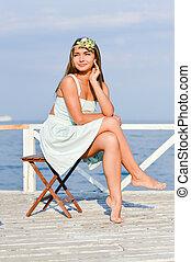 Young beautiful stylish fashion woman sitting on sea pier