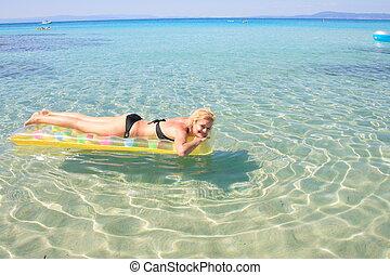 Young beautiful tanned woman in bikini by the sea