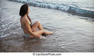 young beautiful tanned woman in bikini sitting on the beach....