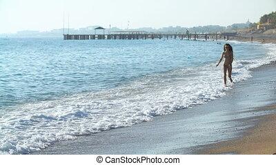 young beautiful tanned woman with long hair in bikini running on sandy beach