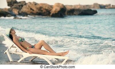 young beautiful tanned woman with long hair in bikini lying...