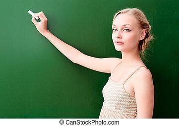 teacher writes on the blackboard with chalk