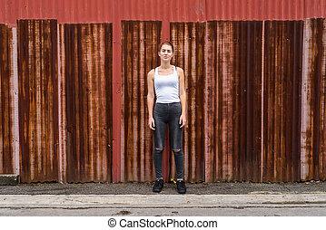 Young beautiful teenage girl standing against old rusty sheet wa