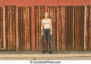 Young beautiful teenage girl standing against old rusty sheet wall