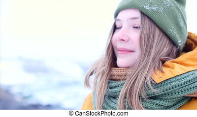 Young beautiful teenage girl teenage with blond hair, enjoying winter day outdoors, girl with a green and brown scarf in a green hipster hat, throws up the snow, looking at the camera. Slow motion