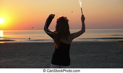 Young beautiful teenager female dancing in the twilight on a beach with a firework candle