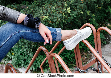 teenager girl is sitting on metal rods, bicycle parking, rock 'n' roll. rock style. female leg and hand close-up