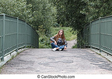 young beautiful teenager girl is sitting on the track on a bridge, rock 'n' roll. rock style.