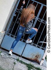 young beautiful teenager girl standing on background of openwork lattice, rock 'n' roll. rock style.
