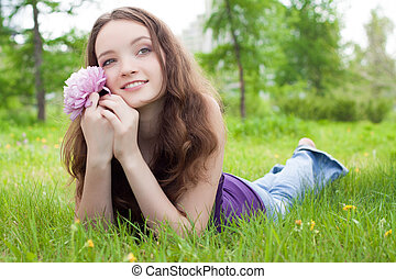 young beautiful teenager with pink flower on lawn
