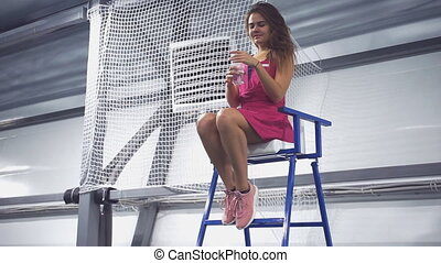 Young beautiful tennis player sits on a chair and drinks...