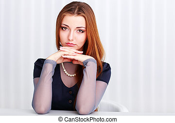 Young beautiful thoughtful woman sitting at the table isolated on a white background
