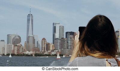 Young beautiful tourist girl taking photos of Manhattan in...