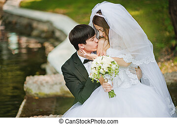 Young beautiful wedding couple at the lake