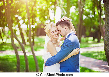young beautiful wedding couple in the park