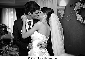 young beautiful wedding couple passionately kissing in the hall