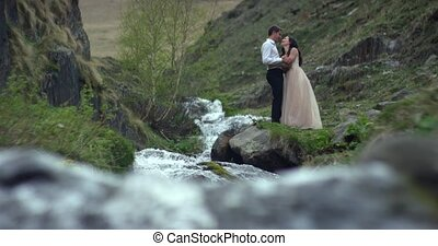 Young beautiful wedding couple standing near the waterfall. Wedding day. Slow motion