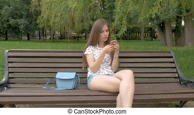 Young beautiful white girl is sitting on a park bench....