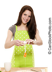 young beautiful woman adding egg to flour on white background