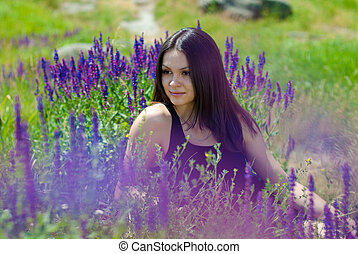 Young beautiful woman among purple flowers