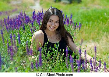 Young beautiful woman among purple flowers