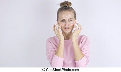 Young beautiful woman applying cream on her face. Skincare...