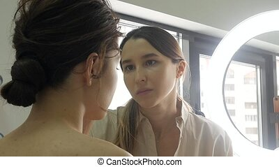 Young beautiful woman applying make-up by make-up artist