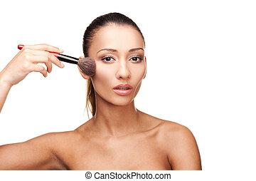 Young beautiful woman applying makeup