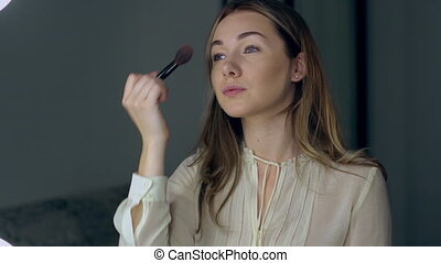 Young beautiful woman applying makeup with brush
