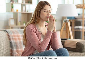 young beautiful woman at home praying with hands together