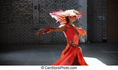 Young beautiful woman ballerina dancing in the hangar. Mid shot