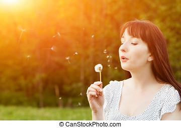 Young beautiful woman blowing a dandelion in spring scenery